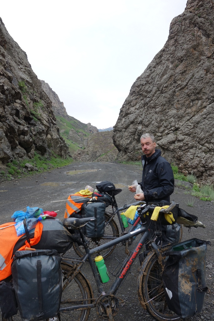 """Die Schlammpassage liegt hinter uns, die Räder sind fast schon wieder """"sauber"""" geregnet und hinter diesem Felstor beginnt die eigentliche, die düstere, gruselige endlose Abfahrt zur afghanischen Grenze."""